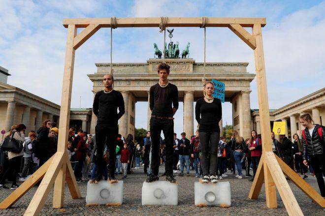 Activistas encima de tres bloques de hielo en la Puerta de Brandemburgo.