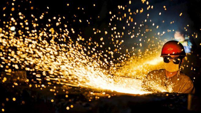 河南洛阳一位工人在加工钢材