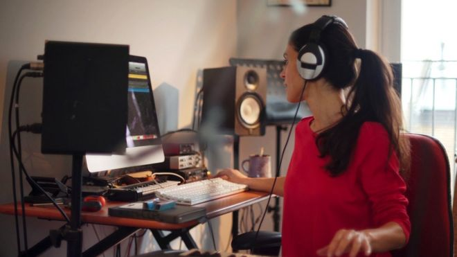 A woman with headphones on and surrounded by music equipment sits at her computer