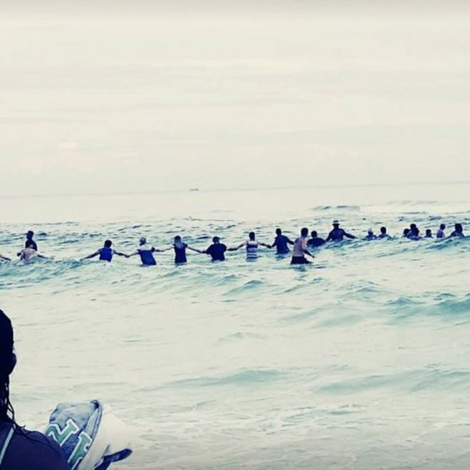 55389a7f19e Image of people holding hands in the water to save drowning family
