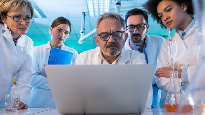 Team of scientists look at a laptop