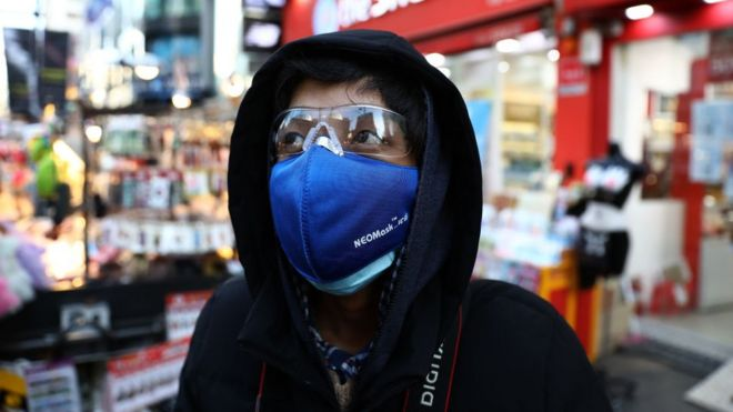 A man wears mask to prevent the coronavirus (COVID-19) walk along the Myungdong shopping district