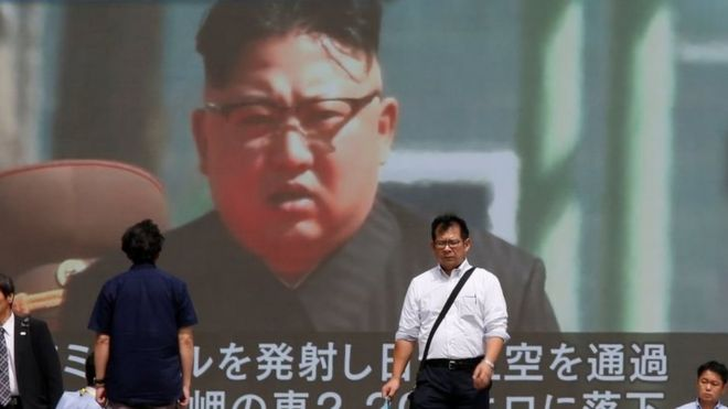 Passersby walk past a TV screen reporting news about North Korea's missile launch in Tokyo, Japan on 15 September 2017.