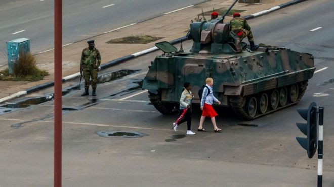 Young women walk past an armoured personnel carrier in Harare, 15 November
