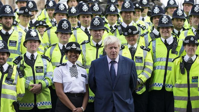 Boris Johnson standing with dozens of police officers