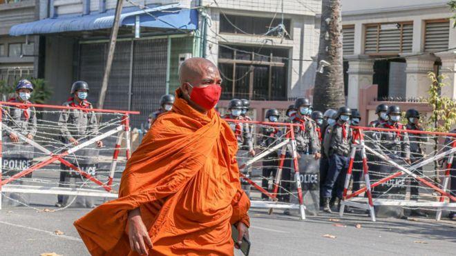 Một nhà sư trước hàng rào cảnh sát dựng lên để chặn người biểu tình ở Mandalay hôm 24/2/2021