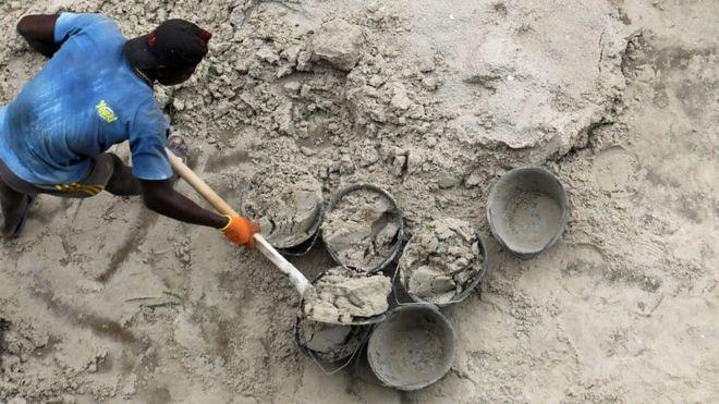 Un homme qui ramasse du sable