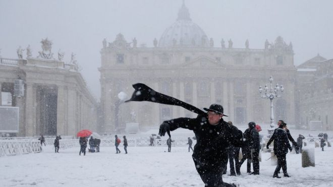 A young priest throws a snowball in St Peter's Square, Vatican