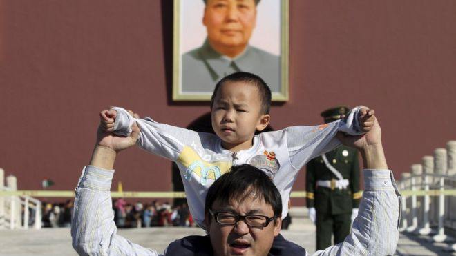 "A boy sits on his father""s shoulders as they pose for a photograph in front of the giant portrait of late Chinese chairman Mao Zedong on the Tiananmen Gate, in Beijing, China, October 2, 2011."