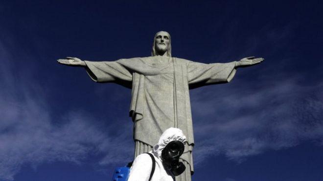 Homem todo coberto pro trajes sanitários em frente à estátua do Cristo Redentor