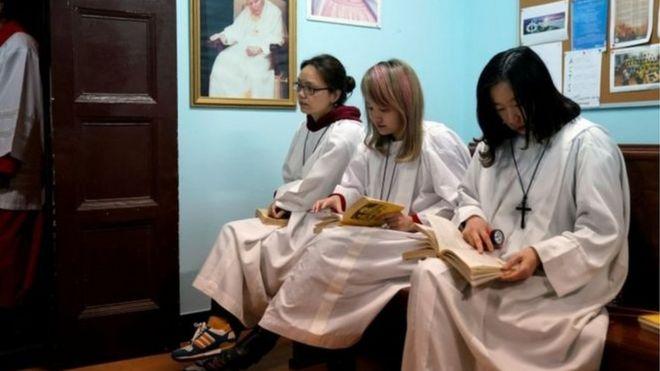 Người Công giáo Trung Quốc ở Thượng Hải ngồi đợi buổi lễ Phục sinh bắt đầu dưới bức ảnh Giáo Hoàng John Paul Đệ Nhị và Đức mẹ Đồng trinh.