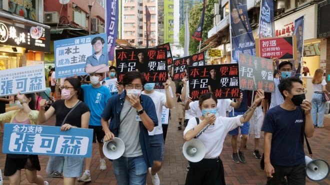 Candidates march on a street to campaign for the primary elections in Hong Kong