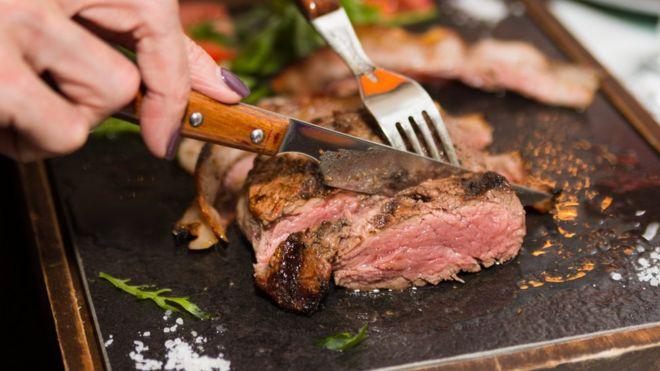 Imagem mostra mulher cortando pedaço de carne com garfo e faca. Algumas dietas com consumo reduzido de carboidratos são ricas nesse tipo de proteína animal, mas pesquisadores sugerem que elas sejam trocadas por proteínas vegetais, mais saudáveis