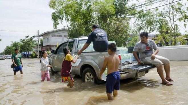 Crianças recebendo garrafas d'água na Tailândia, em área alagada