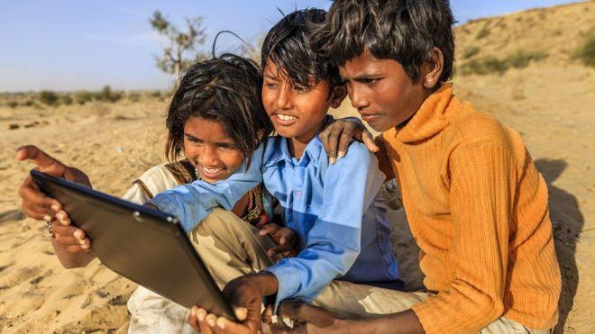 Crianças olham sorrindo para tablet na Índia