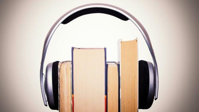 Livros envolvidos por um fone de ouvido