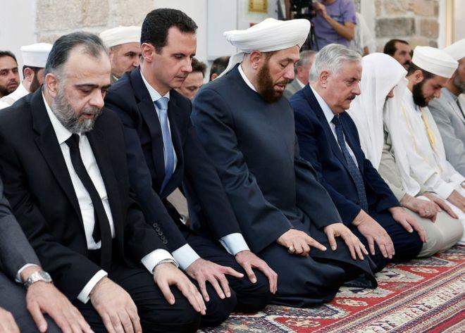 Syrian President Bashar al-Assad (2nd L) attends prayers in Hama, 25 June