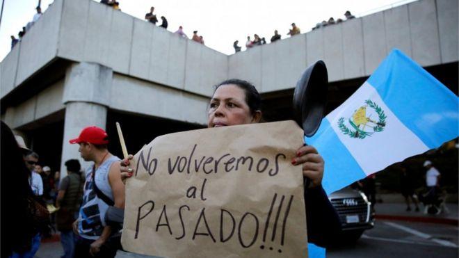 """Una mujer sostiene un letrero que dice """"¡No vamos a volver al pasado!"""" durante una protesta frente al Aeropuerto Internacional La Aurora en apoyo de Yilen Osorio, miembro de la comisión de la ONU contra la corrupción (CICIG) detenido a su llegada al aeropuerto el sábado, en la ciudad de Guatemala, Guatemala, 6 de enero de 2019."""