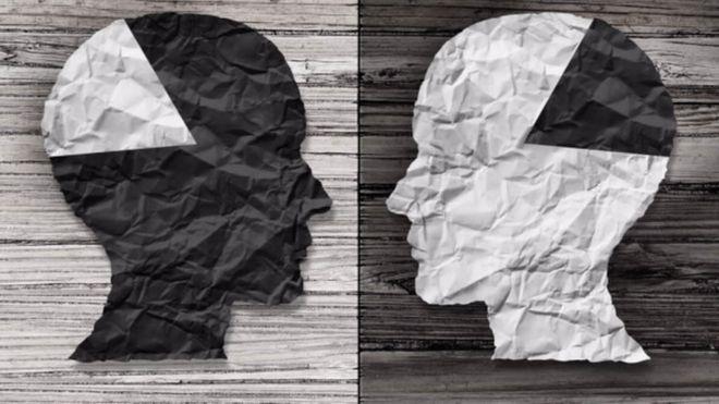 Imagen artística de dos cabezas enfrentadas con parte del cerebro en diferentes colores.