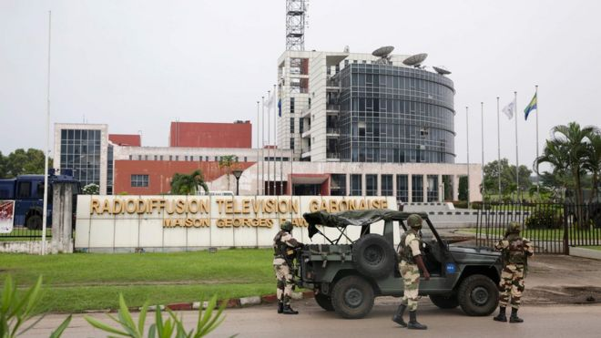 Gabonese soldiers stand in front of the headquarters of the national broadcaster Radiodiffusion Television Gabonaise (RTG) in Libreville