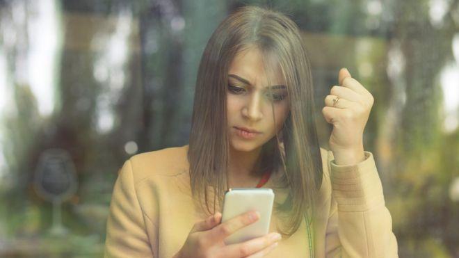 Mujer molesta mirando el celular.