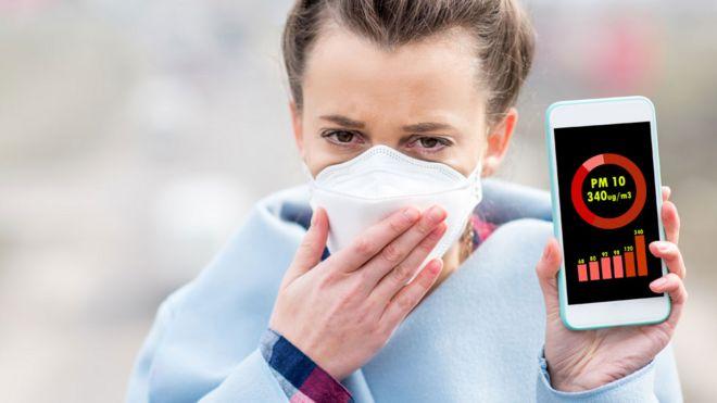 Mujer con una máscara y un celular que muestra el nivel de partículas PM10
