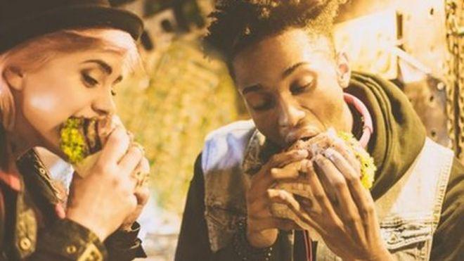 اثنان يأكلان البرغر الغني بالدهون