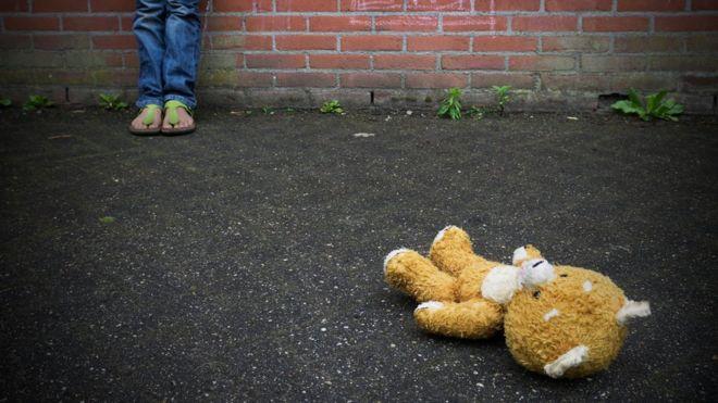 pés de uma criança e um urso de pelúcia jogado no chão