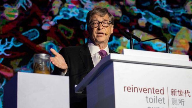 Bill Gates aponta para um pote com cocô, em um evento
