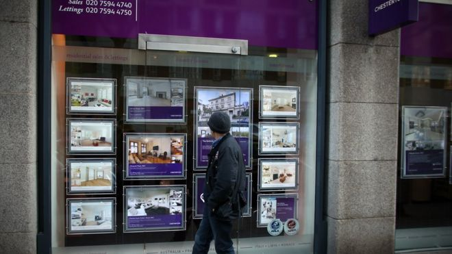 A man walks past an estate agency in West London