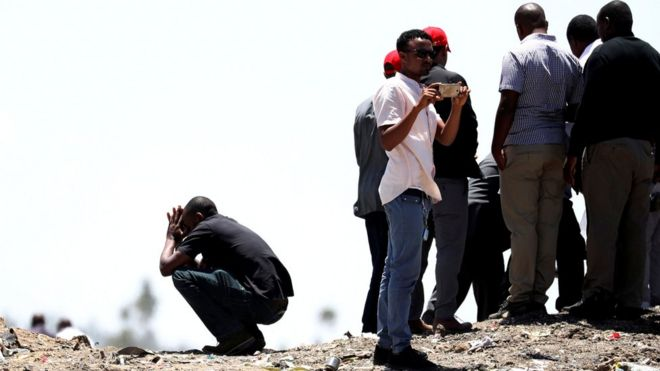 United Nations workers mourn their colleagues during a commemoration ceremony for the victims at the scene of the Ethiopian Airlines Flight 302 plane crash near Addis Ababa Ethiopia