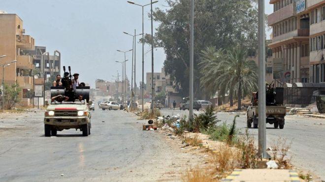 مقاتلون موالون لحكومة الوفاق الوطني الليبية المعترف بها من قبل الأمم المتحدة يركبون في شاحنة على طول طريق في منطقة قصر بن غشير جنوب العاصمة الليبية طرابلس، في 4 يونيو/حزيران 2020