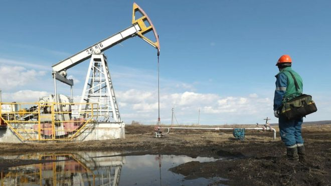 An oil industry worker near an oil pumpjack in Russia