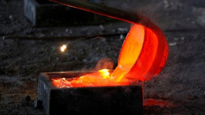 内蒙古一个冶炼厂,工人把稀土金属镧熔化后注入模具。