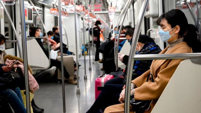 People wearing protective face masks commute on a train in Shanghai.