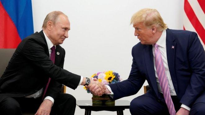الرئيس الروسي فلاديمير بوتين والرئيس الأمريكي السابق دونالد ترامب يتصافحان