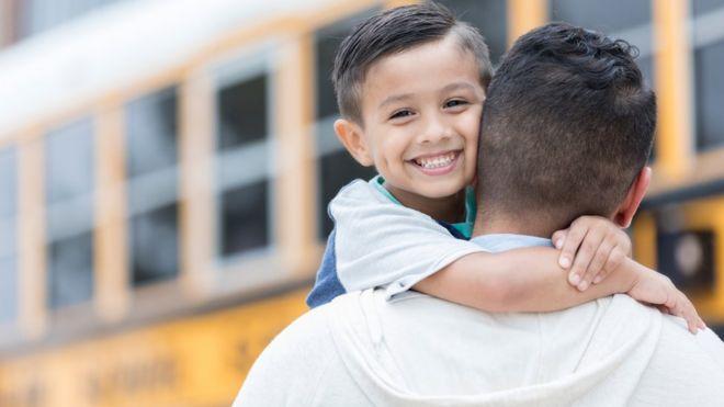 Niño sonríe mientras se abraza al cuello de un hombre