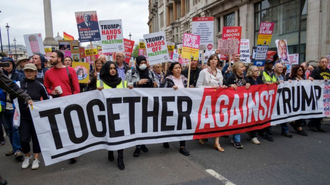 """""""Juntos contra Trump"""" dice el cartel que lleva una multitud mientras marcha por el centro de Londres, Reino Unido, en contra de la visita de Donald Trump."""