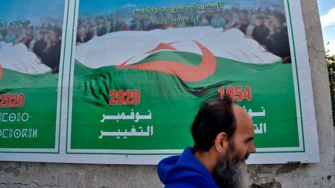 رجل يمر أمام لافتة دعائية للتعديلات الدستورية