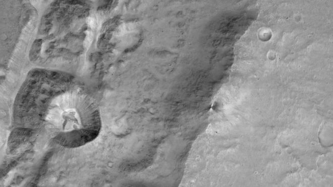 A CaSSIS image of a 1.4km sized crater (left centre) on the rim of a much larger crater near the Mars equator