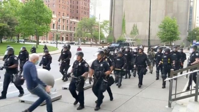 Still image from video of elderly man being pushed by police