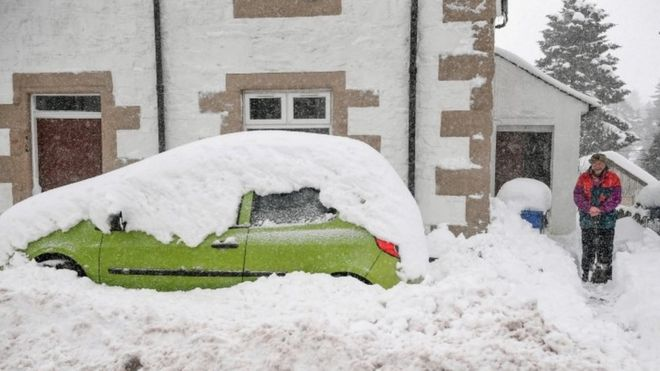 A man clears snow fall from his front door on January 17, 2018 in Leadhills, Scotland