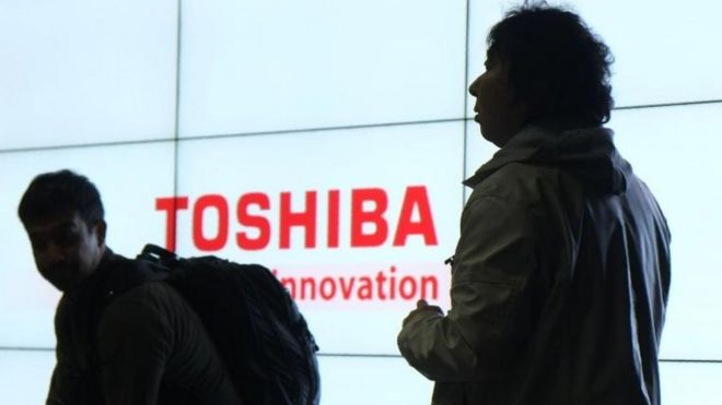 Journalists in front of a Toshiba sign