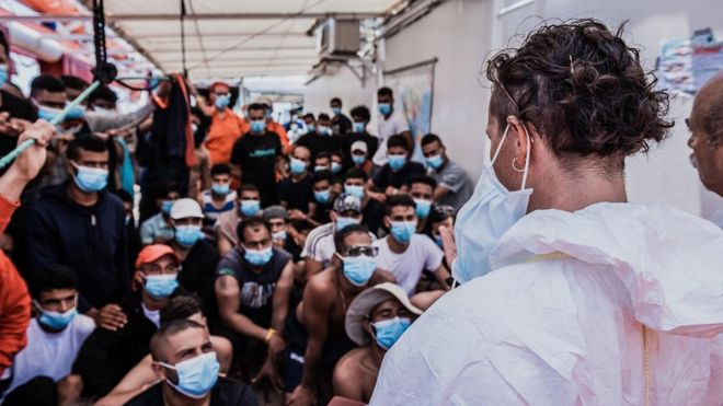 Migrants wearing masks onboard the Ocean Viking