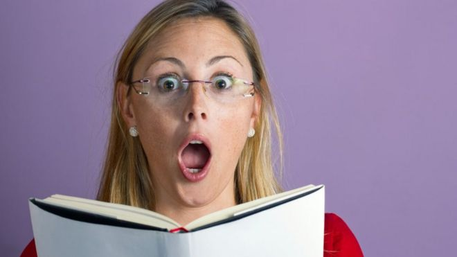 photo shows a woman reading a book with a shocked expression