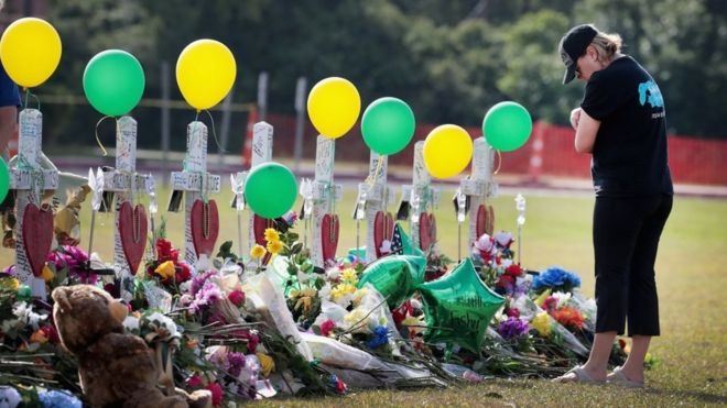Mourners visit a memorial in front of Santa Fe High School on May 22, 2018