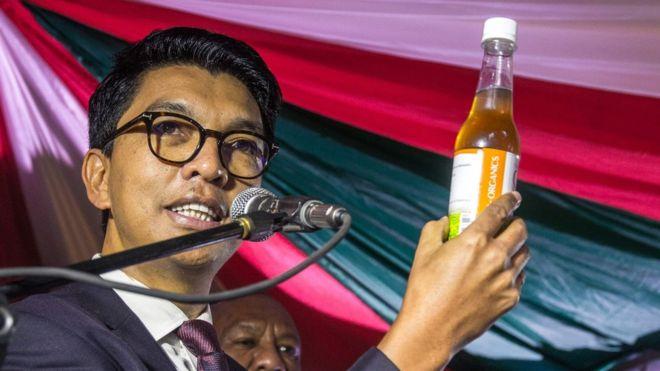 رئيس مدغشقر يحمل زجاجة من المشروب