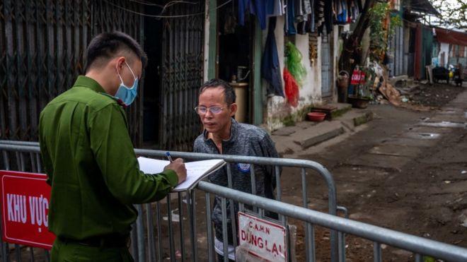 Cảnh sát kiểm tra danh tính một cư dân sống trong khu cách ly ở quận Cầu Giấy, Hà Nội