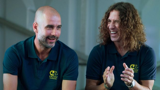 Former Barcelona player Carles Puyol (right) at an event in Madrid in May 2018 talking to Manchester City coach Pep Guardiola (left)