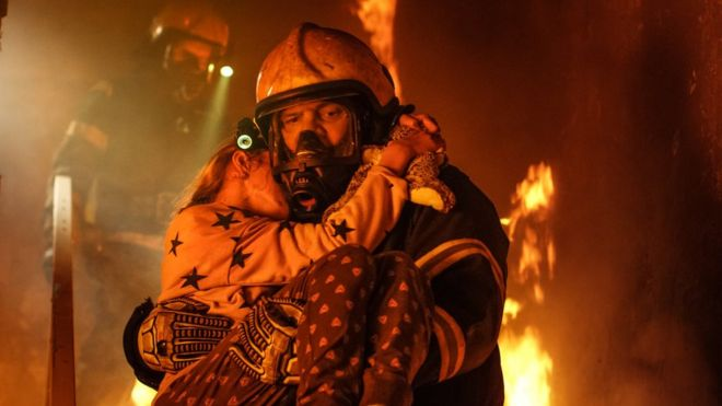 Fireman carrying child